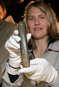 Jedna z archeoložek pózuje s prehistorickým dildem nalezeným v Německu